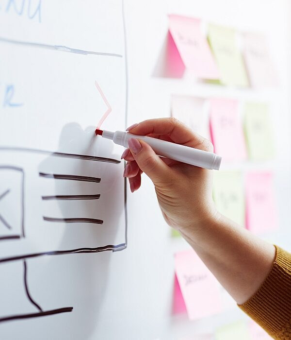 Female web developer with red marker planning website on whiteboard